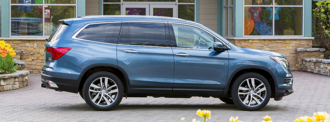 2018 Honda Pilot Elite trim exterior shot blue paint color side shot parked in front of a zoo shop with yellow flowers in front