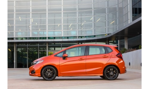 2019 Honda Fit exterior side shot orange parked in front of a glass gridded building