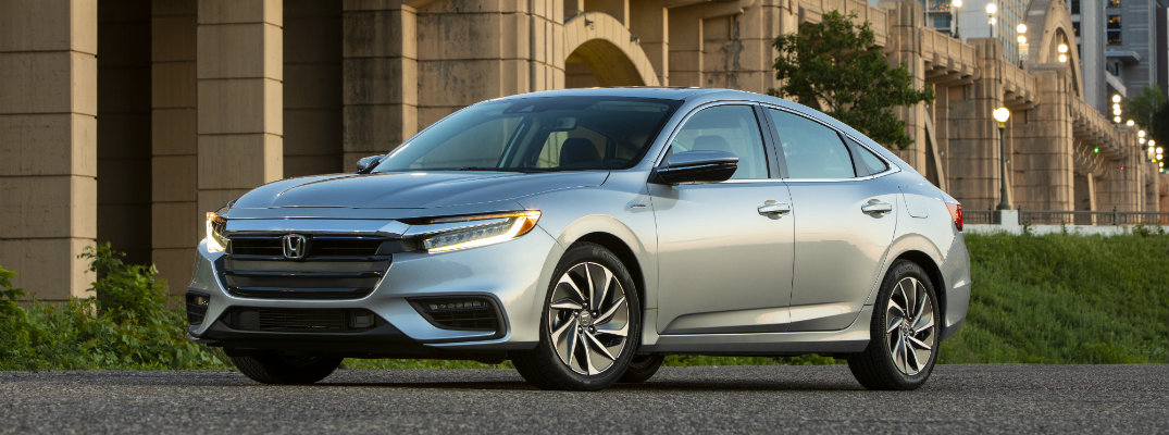 2019 Honda Insight exterior shot silver parked on a gravel trail below a bridge and skyscraper city skyline