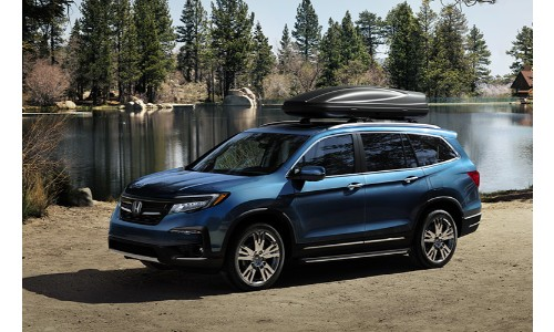 2019 Honda Pilot exterior shot blue paint job parked on a beach near a forest lake with cargo strapped to the roof