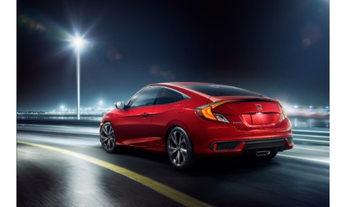2019 Honda Civic Coupe Sport exterior rear shot with red paint job on a highway at night