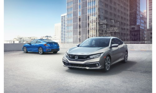 2019 Honda Civic and Coupe exterior shot parked on a top of a building with the sun and skyscrapers in the background