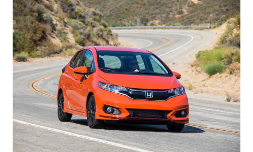 2019 Honda Fit exterior shot orange driving down a desert highway curving with metal rails