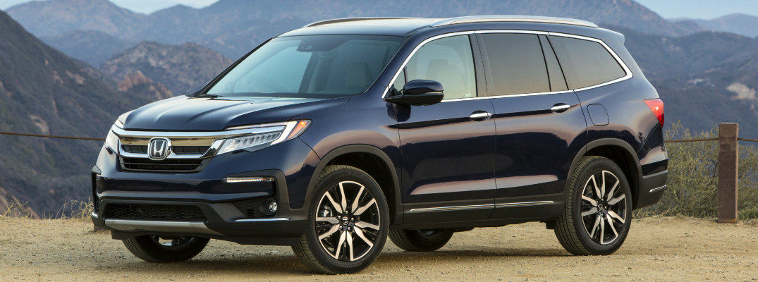2019 Honda Pilot exterior shot with dark blue paint color parked on a dirt path in the mountains