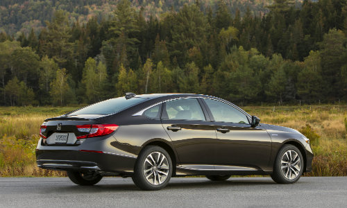 2018 Honda Accord Hybrid sedan exterior back bumper and trunk shot parked in clearing of grass forest and mountain background