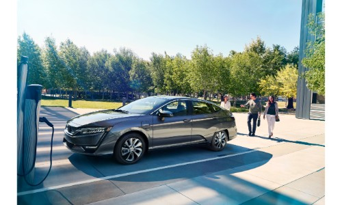 2018 Honda Clarity Electric exterior shot parked at a charging station as a family approaches it
