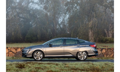 2018 Honda Clarity Plug-In Hybrid exterior side shot parked on a forest road with a stone wall behind it