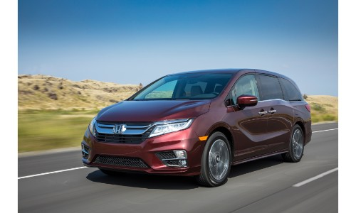 2019 Honda Odyssey Exterior Shot With Red Metallic Color Paint Job Driving  Down A Country Highway
