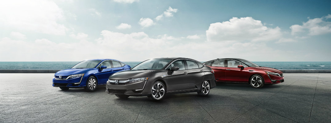 Honda Clarity Series of Electric, Fuel-Cell, and Plug-In Hybrid exterior line up on a concrete plateau by the sea under a cloudy sky