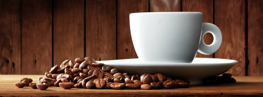 a cup of hot coffee on a platter on a wooden table near a pile of coffee beans