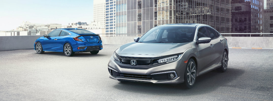 2019 Honda Civic Sedan and Coupe exterior shot with silver and blue paint colors parked on the roof of a building parking garage with skyscrapers behind them