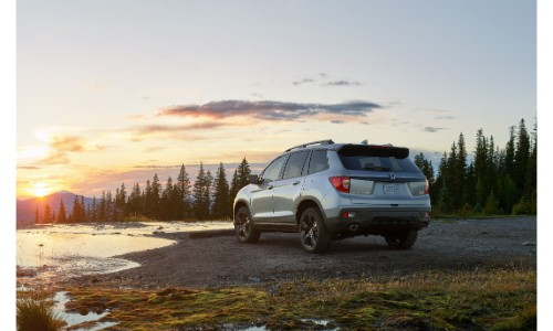 2019 Honda Passport SUV exterior rear shot of bumper parked on a beach near a lake and forest at sunset