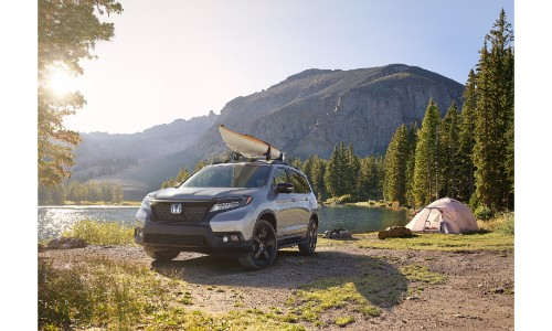 2019 Honda Passport SUV exterior shot with silver paint color with a kayak strapped on roof rails parked in a forest wilderness with mountains in the background