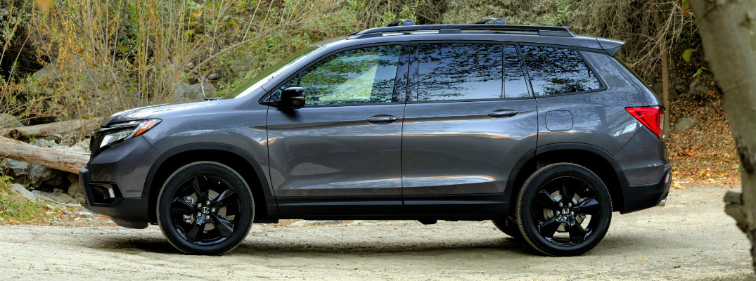 2019 Honda Passport exterior side shot with dark gray paint color parked on a stone cliff and surrounded by wilderness brush