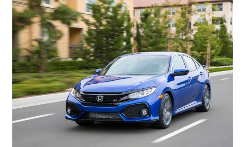 2019 Honda Civic Si sedan exterior shot with blue paint color driving by apartment buildings with walls of green brush