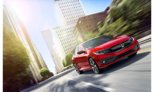 2019 Honda Civic sedan exterior shot with red paint color driving through an urban city under the glare of a bright sun