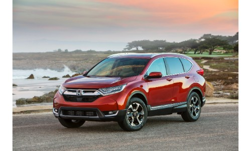 2019 Honda CR-V exterior shot with red orange paint color parked on a beach near the sea as the sun sets