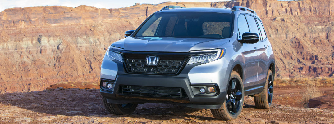 2019 Honda Passport exterior shot with lunar silver metallic paint color parked at the top of an orange rock canyon