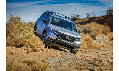 2019 Honda Passport exterior shot with silver gray paint color and roof rail package driving over rocky off-road terrain