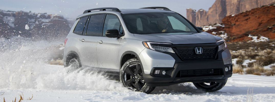 2019 Honda Passport exterior shot with silver metallic paint color driving through a snowy field between mountains