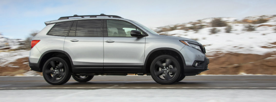 2019 Honda Passport exterior side shot with silver metallic paint color driving on a country highway while passing snowcapped fields and rocky hills