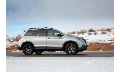 2019 Honda Passport exterior side shot with silver metallic paint color driving on a country highway while passing snowcapped plains and rocky hills