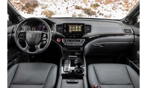 2019 Honda Passport interior shot of front seating, steering wheel, and dashboard layout, with a snowy field seen out of the windshield