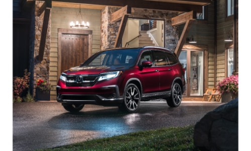2019 Honda Pilot exterior shot with red paint color parked outside a fancy house at night with its headlights on
