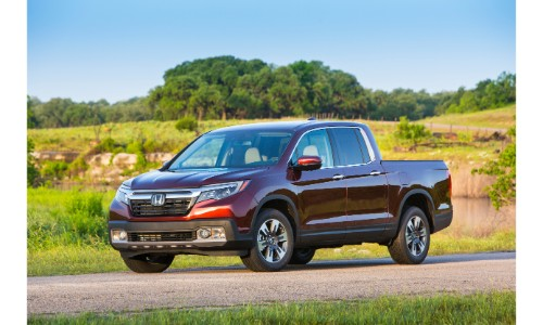 2019 Honda Ridgeline exterior shot with rich red paint color parked on an asphalt road in the country surrounded by tall green grass