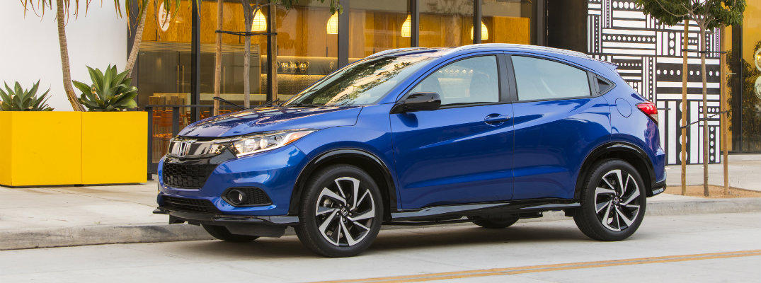 2019 Honda HR-V SUV exterior side shot with blue paint color parked outside a hotel near palm trees