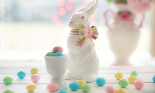 ceramic bunny sculpture surounded by miniature candy eggs on a table