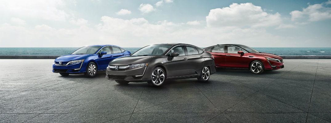 2019 Honda Clarity Electric, Fuel Cell, and Plug-In Hybrid models lined up near the see in blue, gray, and red paint colors