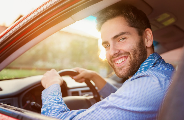 man driving a car and turning to look at camera