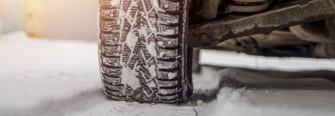 Close Up of a Snow Tire on a Car in Snow