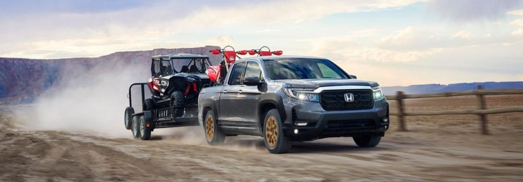 Gray 2021 Honda Ridgeline Towing a Trailer on a Dirt Road