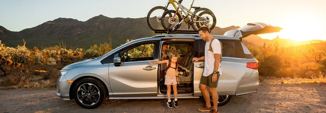 2021 Honda Odyssey with bikes on top and dad and daughter