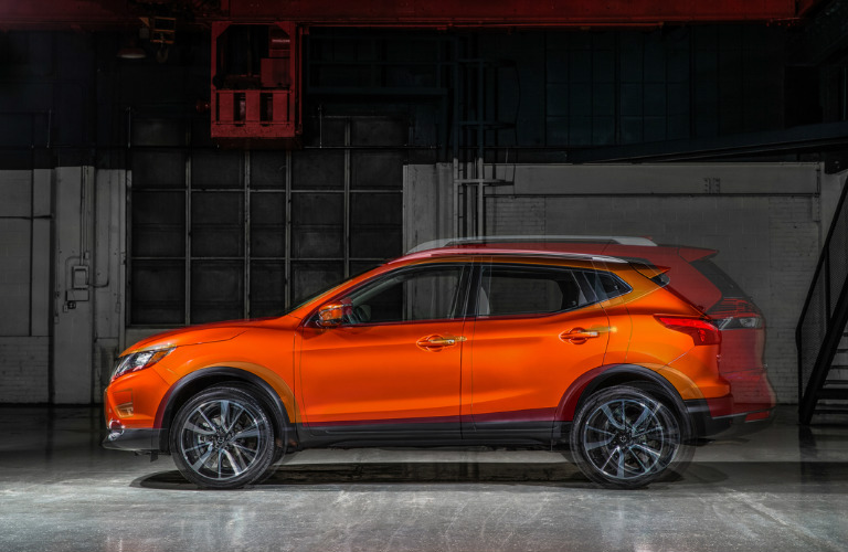 Orange Nissan Rogue Sport and red Nissan Rogue superimposed on each other