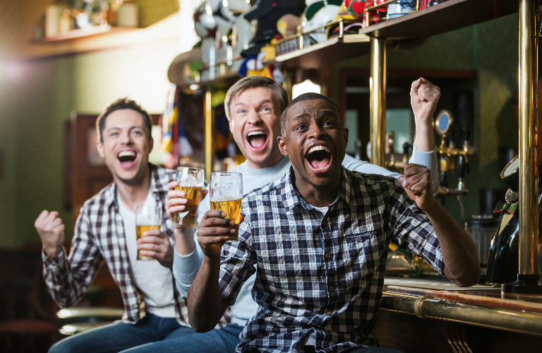 three guys watching sports and cheering in a bar