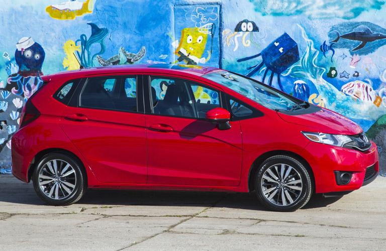 red 2017 Honda Fit parked by wall mural