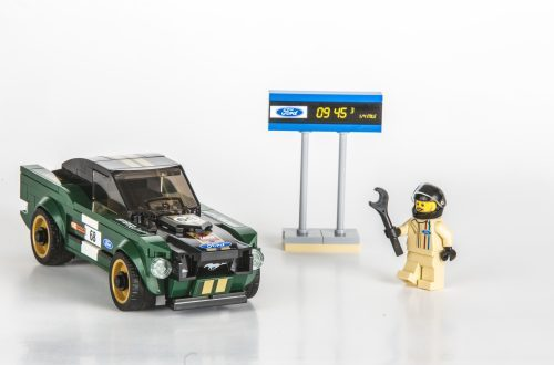 LEGO figure holding a wrench next to the timing board by the 1968 Ford Mustang from the Ford LEGO Speed Champions kit