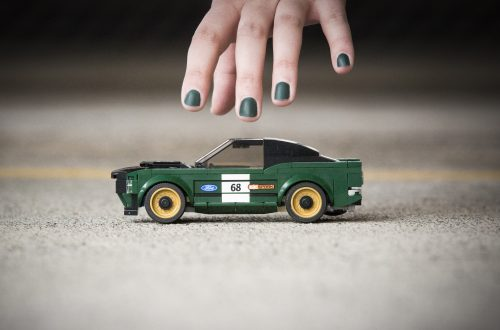 Persons hand with green nail polish reaching down to pick up the 2018 Ford LEGO Speed Champions 1968 Ford Mustang