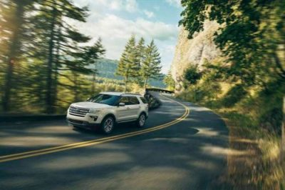 2018 Ford Explorer driving around a corner in a forest