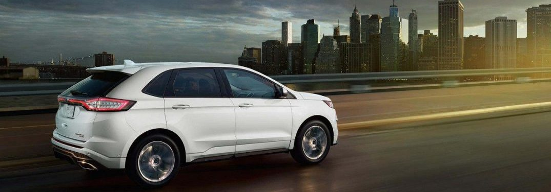 2018 Ford Edge driving towards a city at sunset