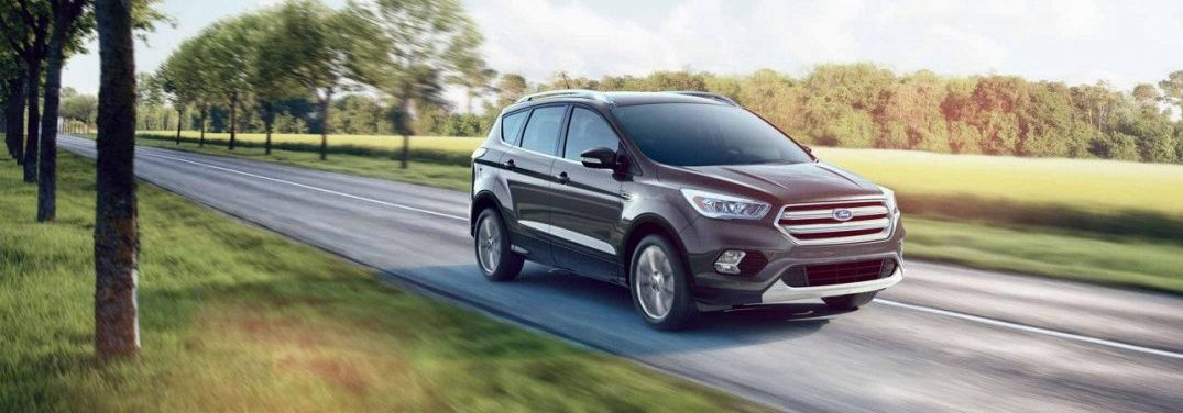 2018 Ford Escape driving quickly on an open highway by a field