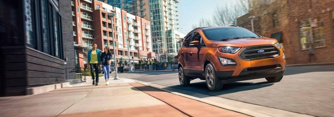 Side profile of the 2018 Ford EcoSport driving in a city next to people walking on a sidewalk