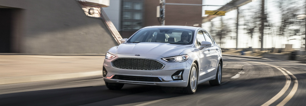 front view of white 2019 ford fusion driving down empty city road