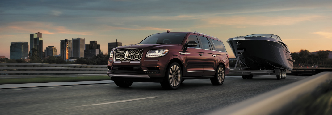 red 2018 lincoln navigator towing large boat on road