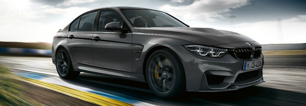 Grey 2018 BMW M3 CS Driving on a Race Track with Puffy Clouds in the Background