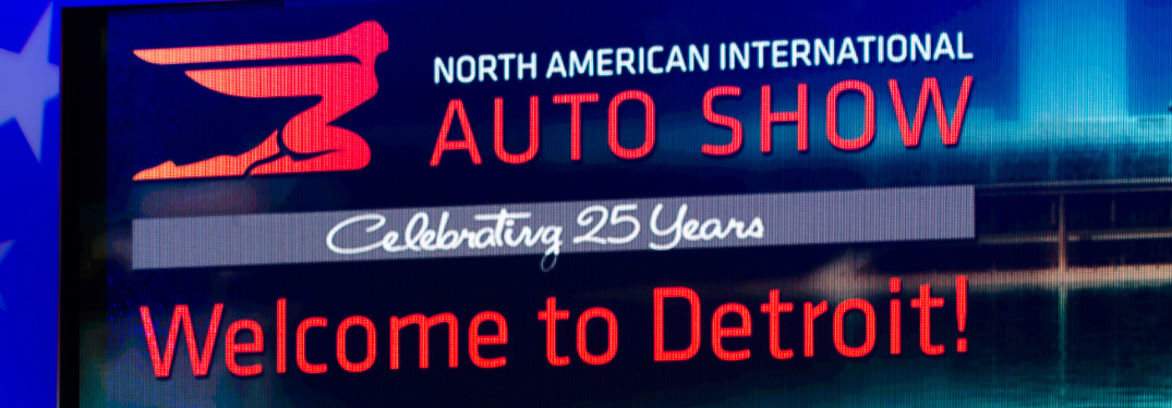 "Large Screen with the Caption, ""North American International Auto Show, Celebrating 25 Years and Welcome to Detroit!"""