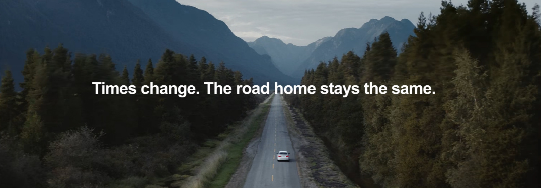 """Times change. The road home stays the same."" caption and BMW drving on Mountainous Road"
